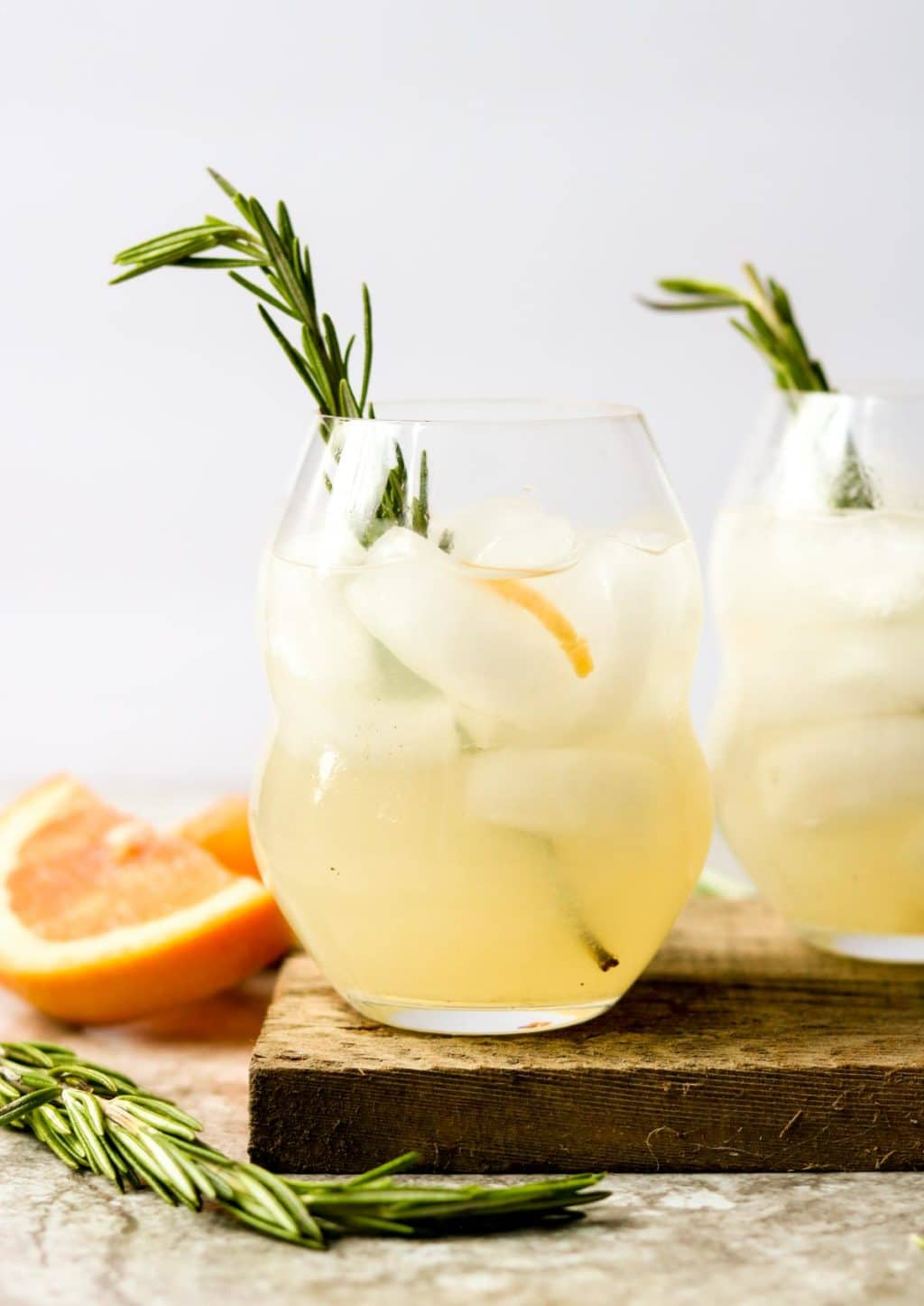 Two glasses of Rosemary Paloma with a rosemary sprig garnish