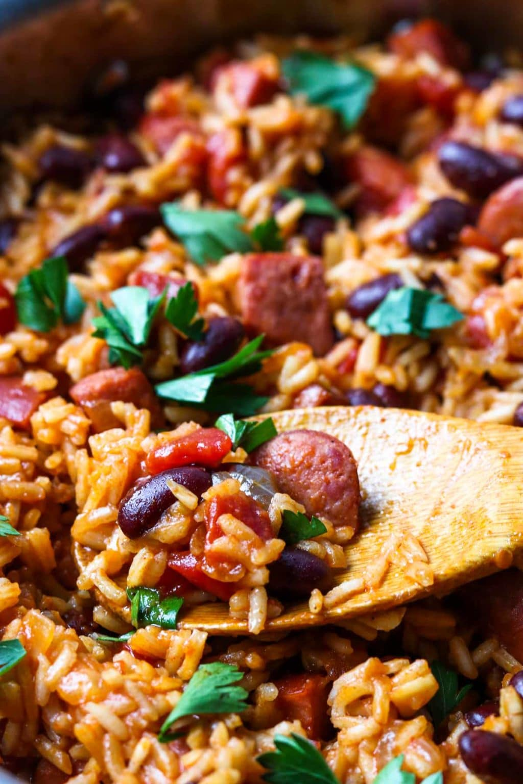 A wooden spoon full of rice, beans, sausage and tomatoes in a pan of dirty rice and beans