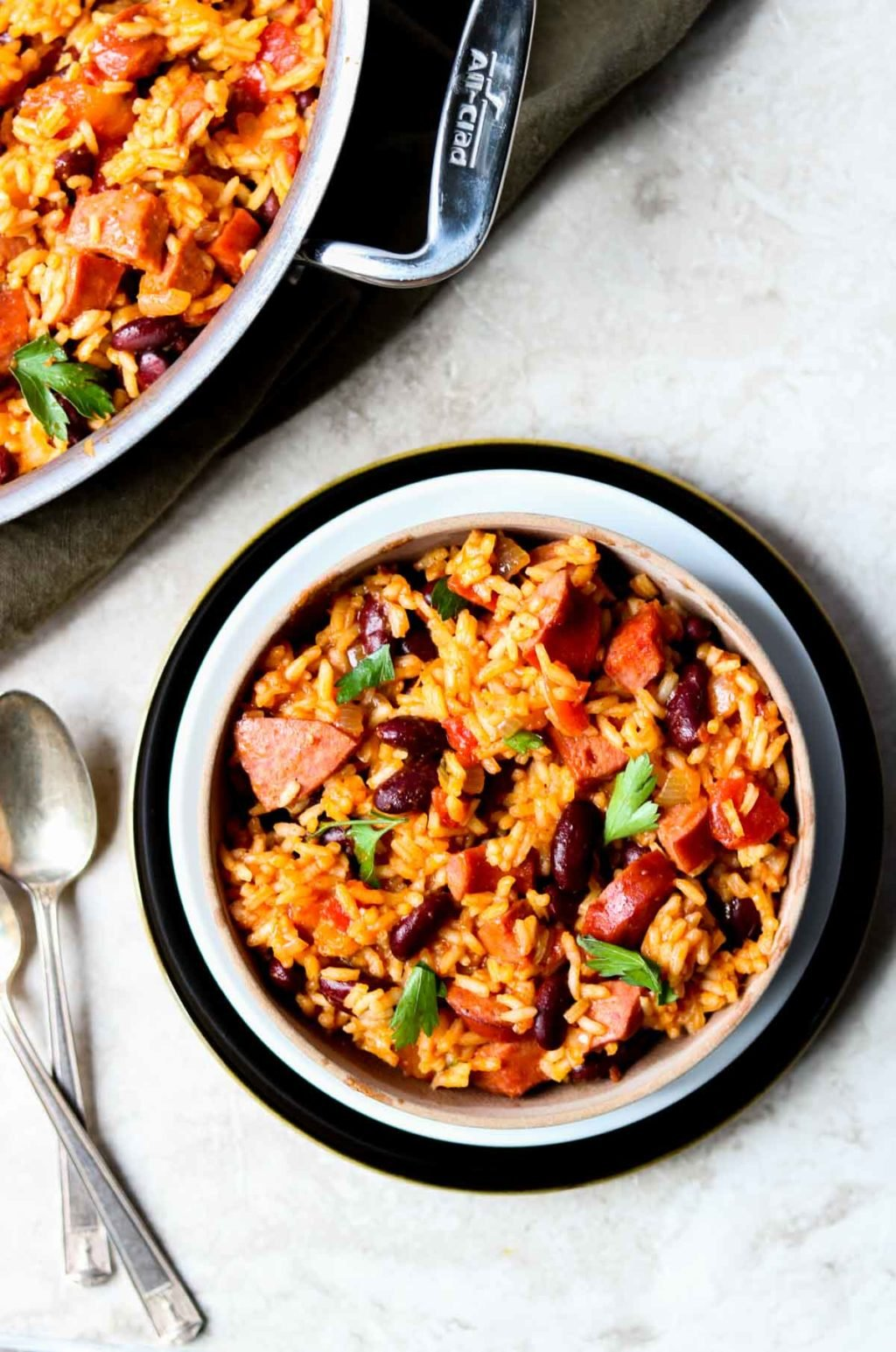 A bowl of dirty rice and beans with two spoons to the side, an all clad skillet at the top of the picture