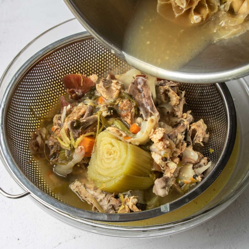 straining the solids from chicken stock