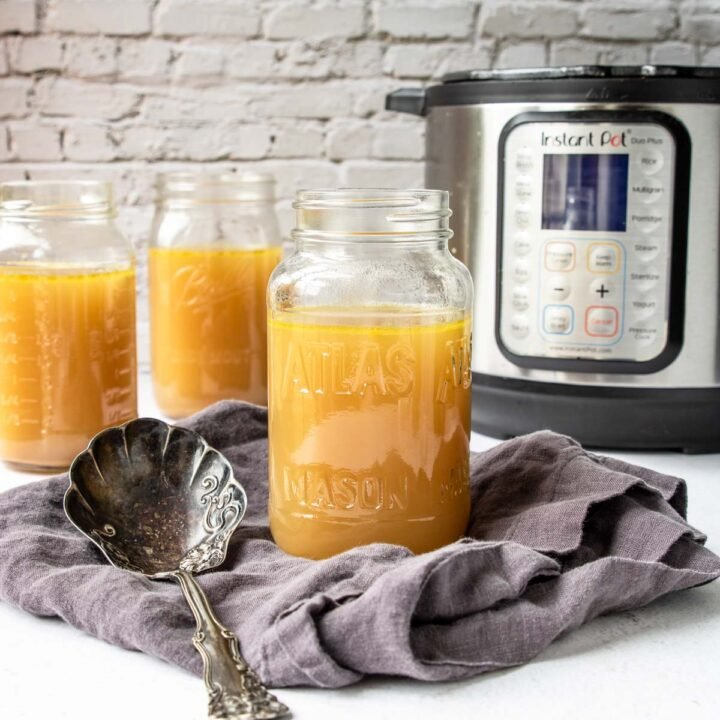 mason jars with chicken stock and an instant pot in the back