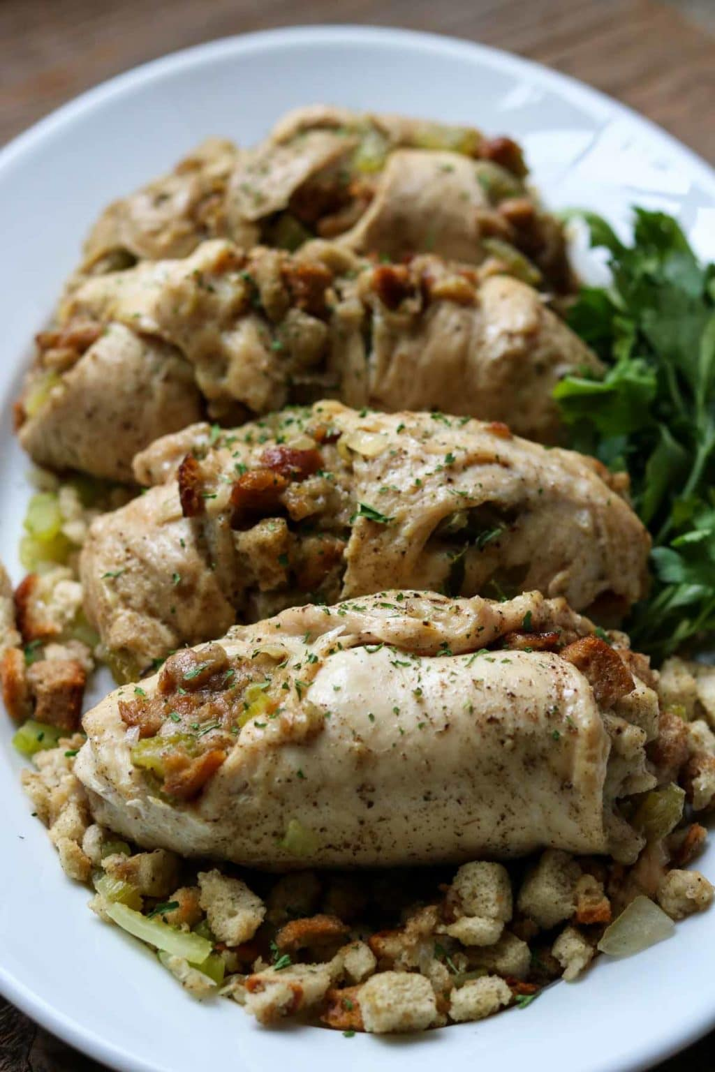 chicken with stuffing on a white oval plate garnished with parsley