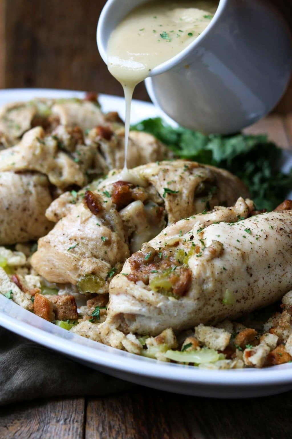 Chicken with stuffing on a white plate with gravy being poured over top