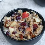 Oatmeal in a black bowl that is full of apples, raisins, pecans and cinnamon