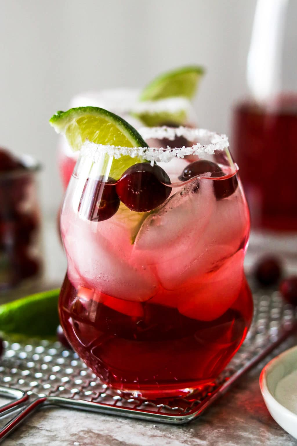 Cranberry Ginger Margarita in a glass garnished with salt, cranberries and limes