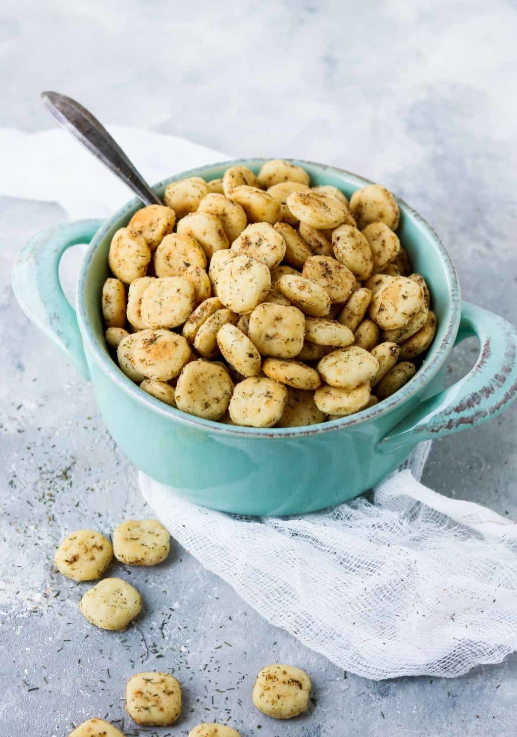 Seasoned oyster crackers in a blue pot with a spoon