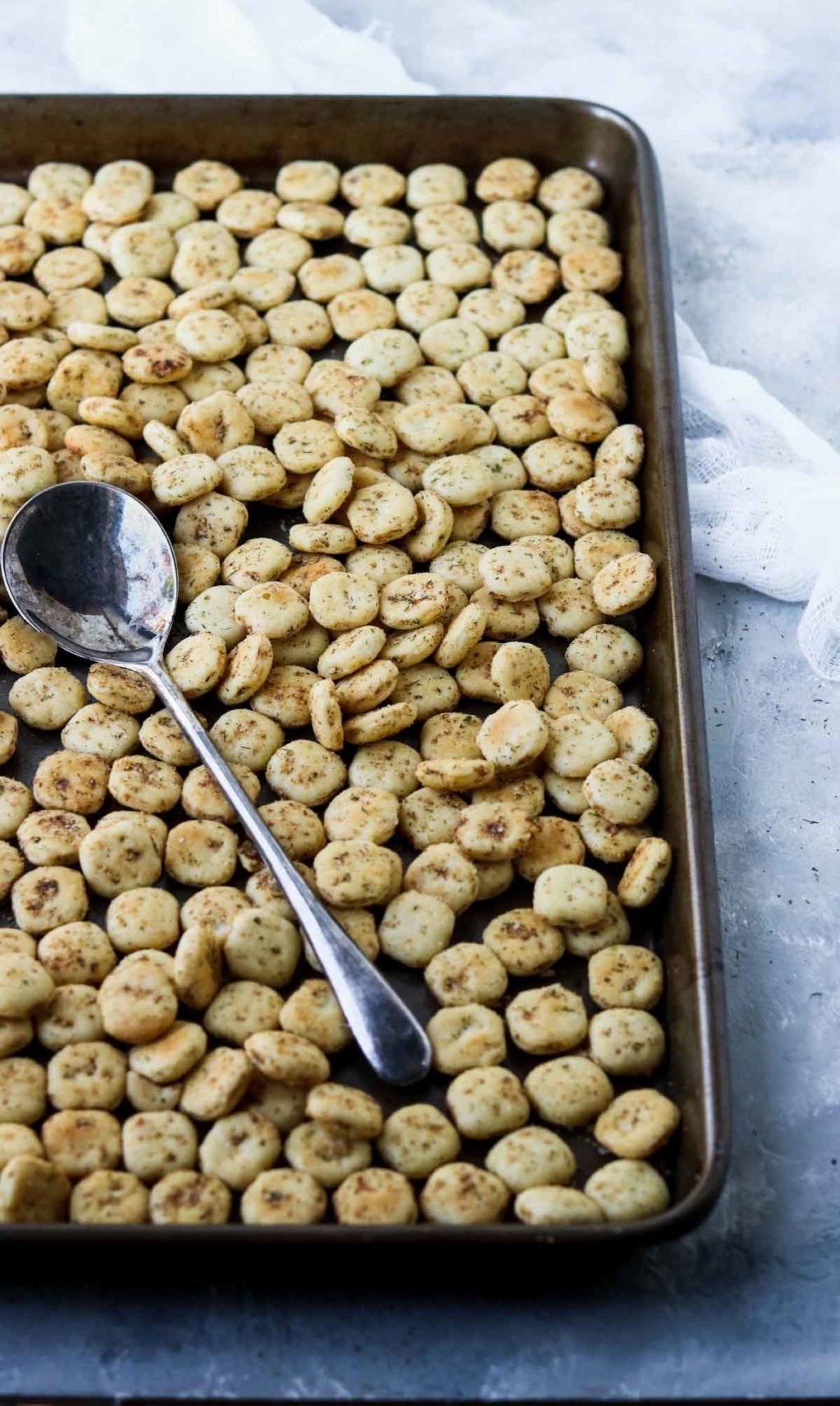 Seasoned Oyster Crackers on a baking sheet with a spoon