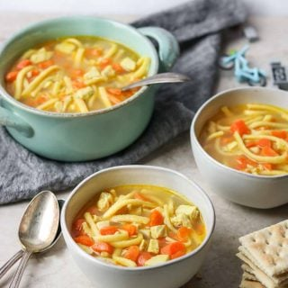 two white bowls of kid friendly chicken noodle soup with two spoons, a large pot of chicken noodle soup sitting on a towel