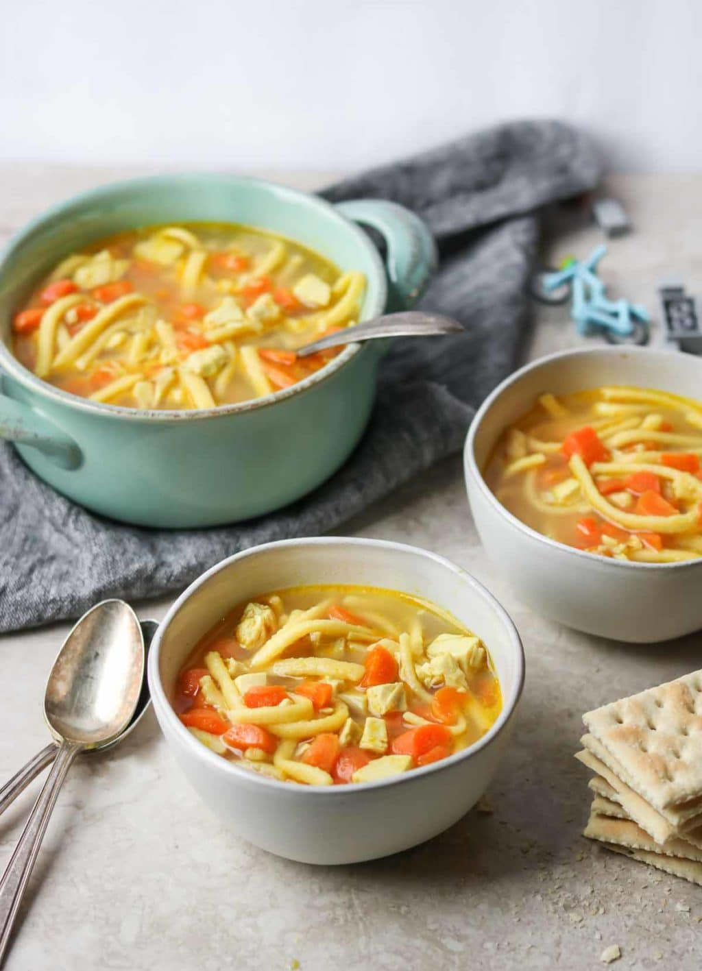 two white bowls of kid friendly chicken noodle soup with two spoons, a large pot of kids chicken noodle soup sitting on a towel