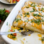 veggie enchiladas being served from a white casserole pan