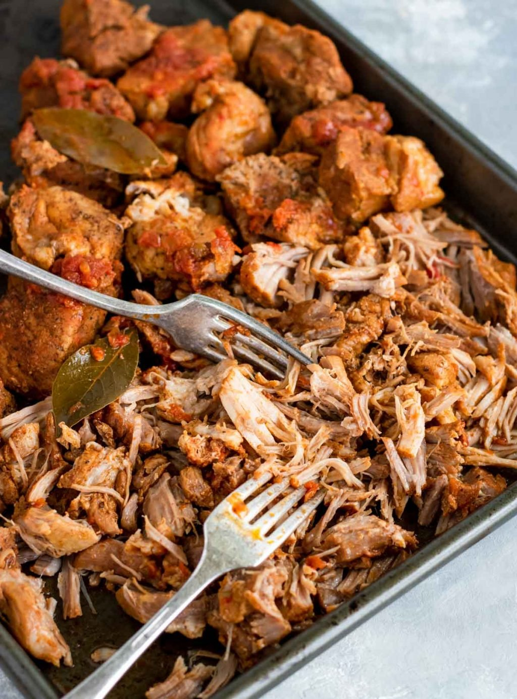 pressure cooker carnitas on a baking sheet with two forks