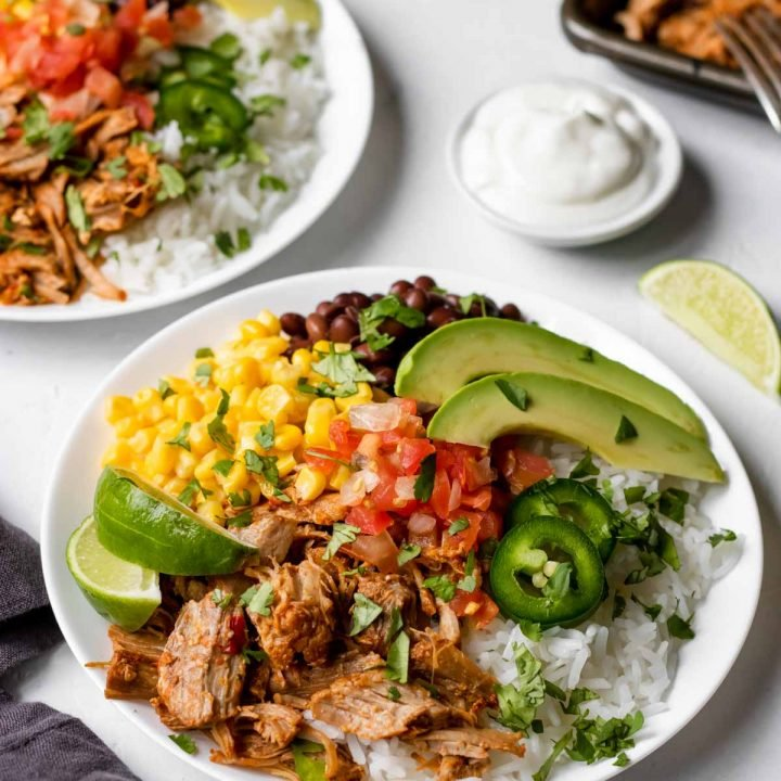 Carnitas burrito bowl garnished with cilantro, limes, avocado.