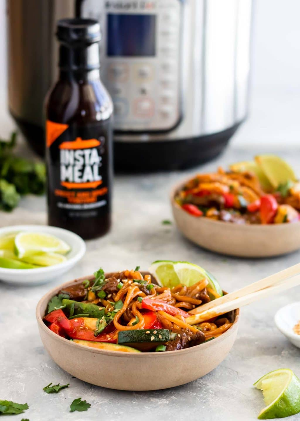 Teriyaki Beef Noodles in a bowl with an Instant Pot in the background