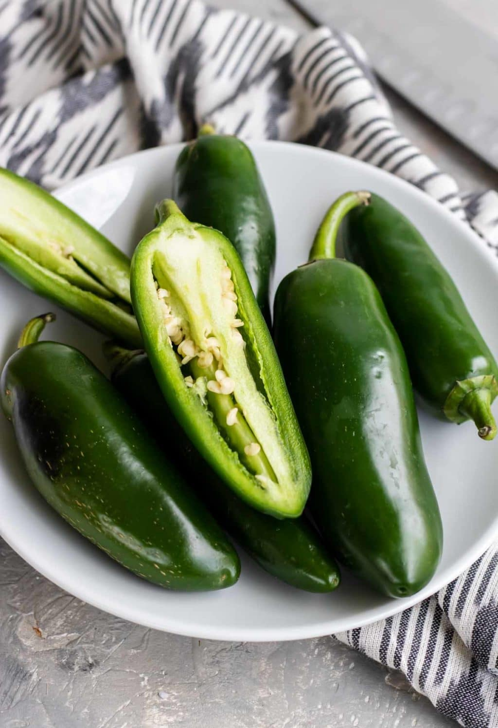 a white bowl of jalapenos with one split in half lengthwise