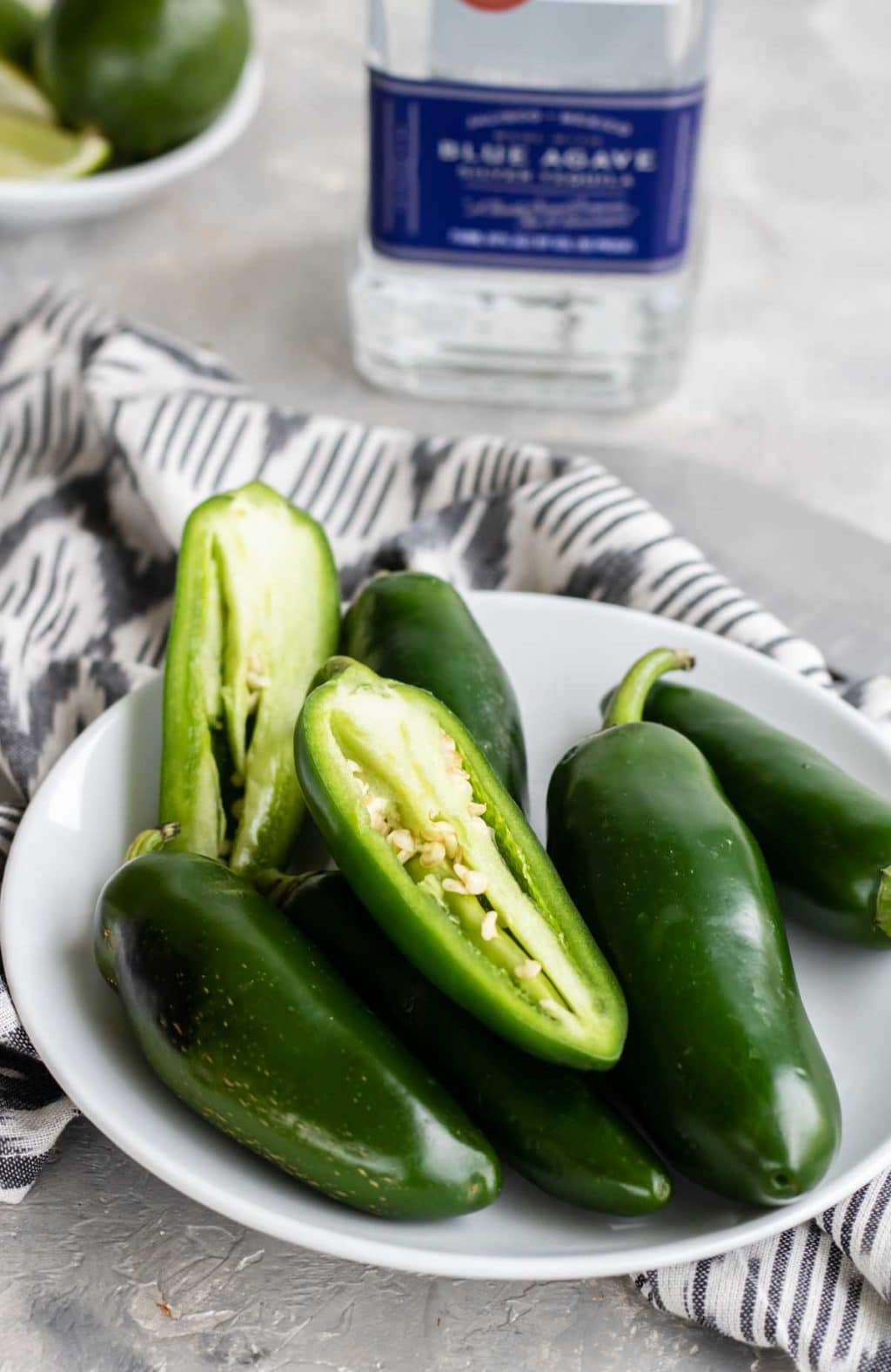 jalapenos in a white bowl with a bottle of tequila in the background