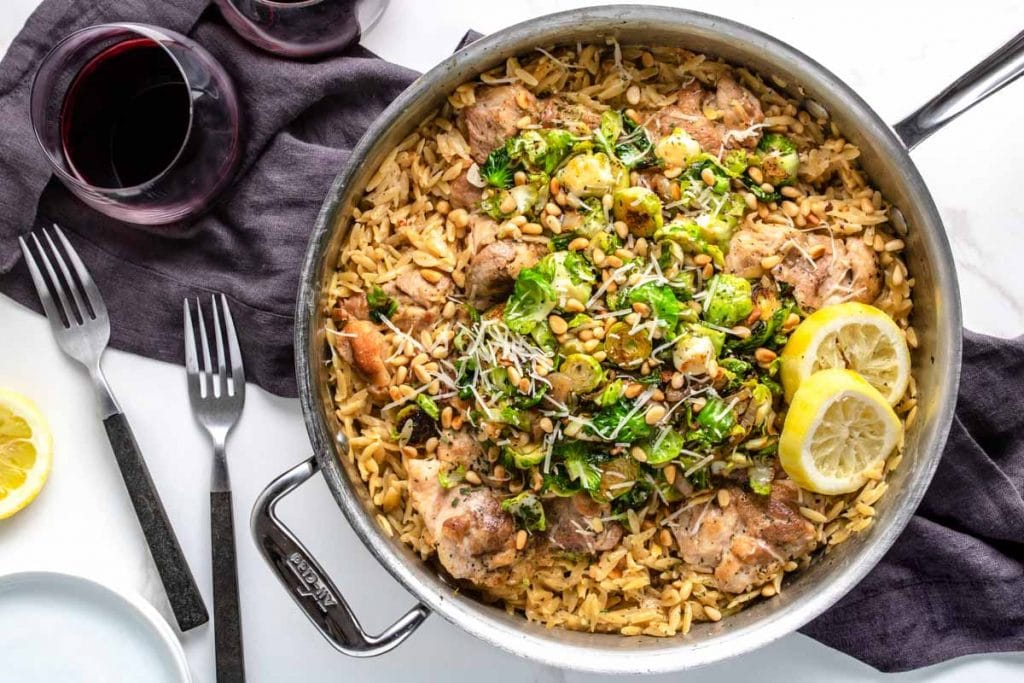 One Skillet Creamy Lemon Orzo with Chicken & Brussels Sprouts with plates and forks and a glass of wine