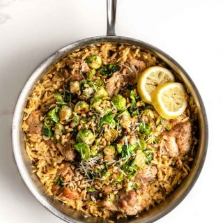 one skillet with lemon orzo and chicken topped with burssels sprouts and pine nuts