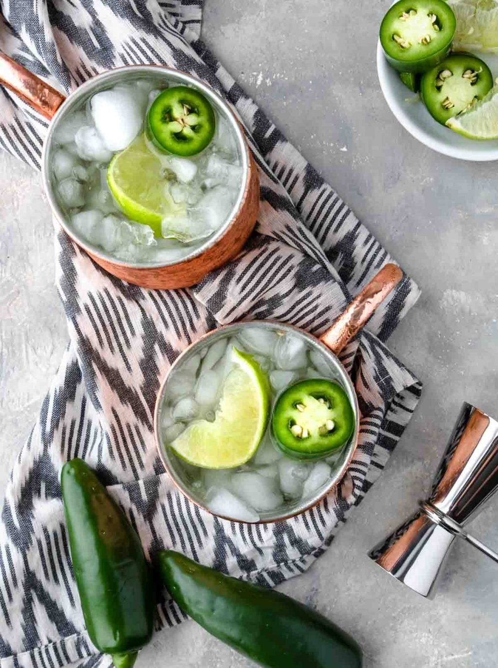 overhead shot of 2 mexican mule cocktails in copper mugsgarnished with limes and jalapenos
