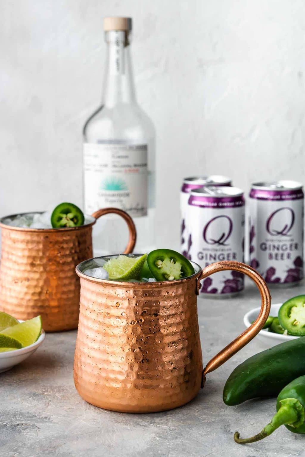 Tequila Moscow Mule in a copper mug with a bottle of tequila, jalapenos and ginger beer