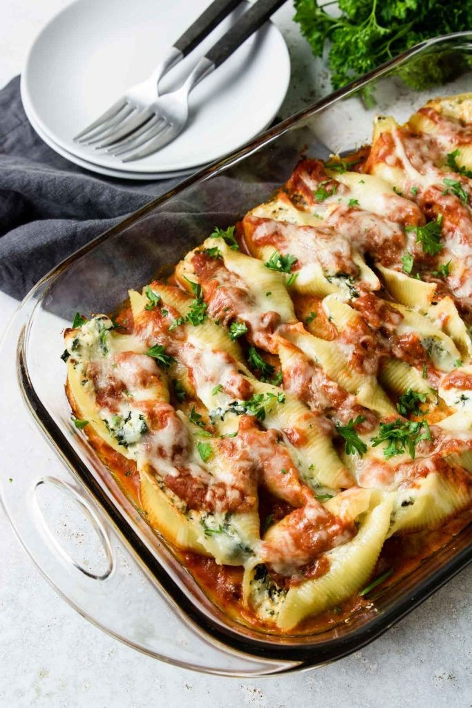 Vegetarian Stuffed Shells in a glass baking dish with two plates and two forks to the side