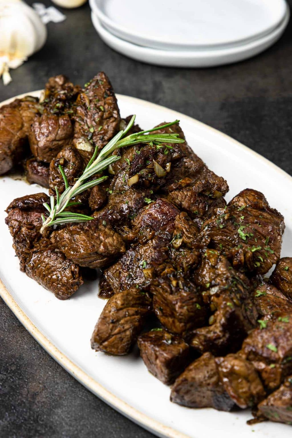 Pan seared steak bites in a garlic butter sauce on a white plate topped with rosemary
