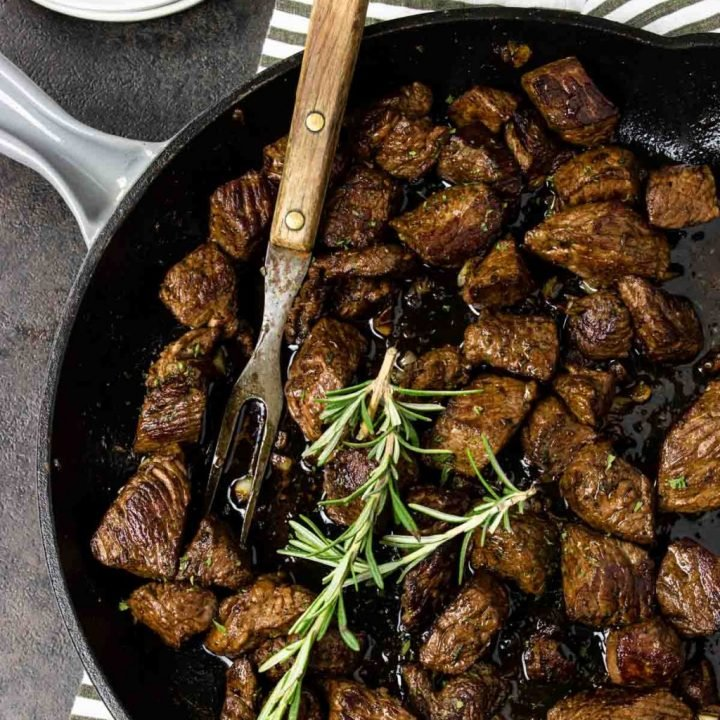 Garlic Butter Steak Bites in a skillet with a meat fork and topped with rosemary