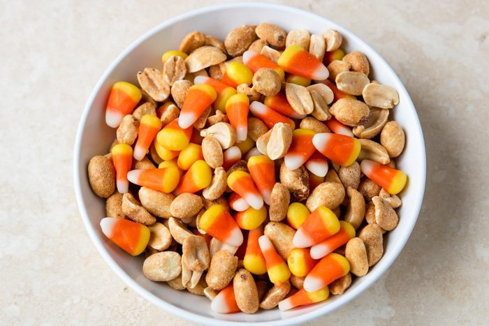 Sweet and salty candy corn snack mix in a white bowl