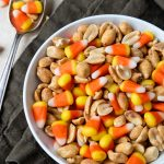 Candy Corn and peanuts mixed in a bowl with a few spilled to the side