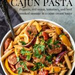 penne pasat, sausage, peppers and onions in a cream sauce in a white bowl.