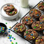 Chocolate Cake Mix Cookies on a cooling rack with milk and a plate of cookies