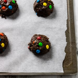 Cake Mix Cookie batter on a parchment lined baking sheet with M&M's pressed into the top