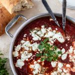 Chicken in a red sauce topped with goat cheese, crusty bread to the side.