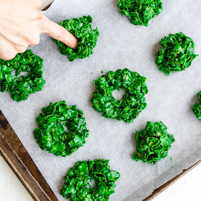 pushing my finger into the center of the cornflake wreath cookies