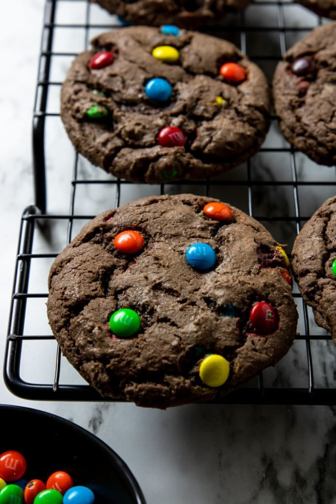 Chocolate M&M cookie on a cooling rack