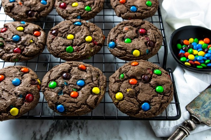 Chocolate Cake Mix Cookies with M&M's cooling on a black wire rack
