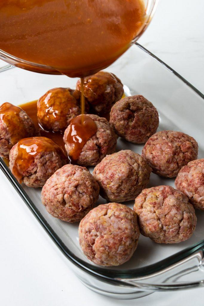 pouring the tomato brown sugar sauce over the ham balls