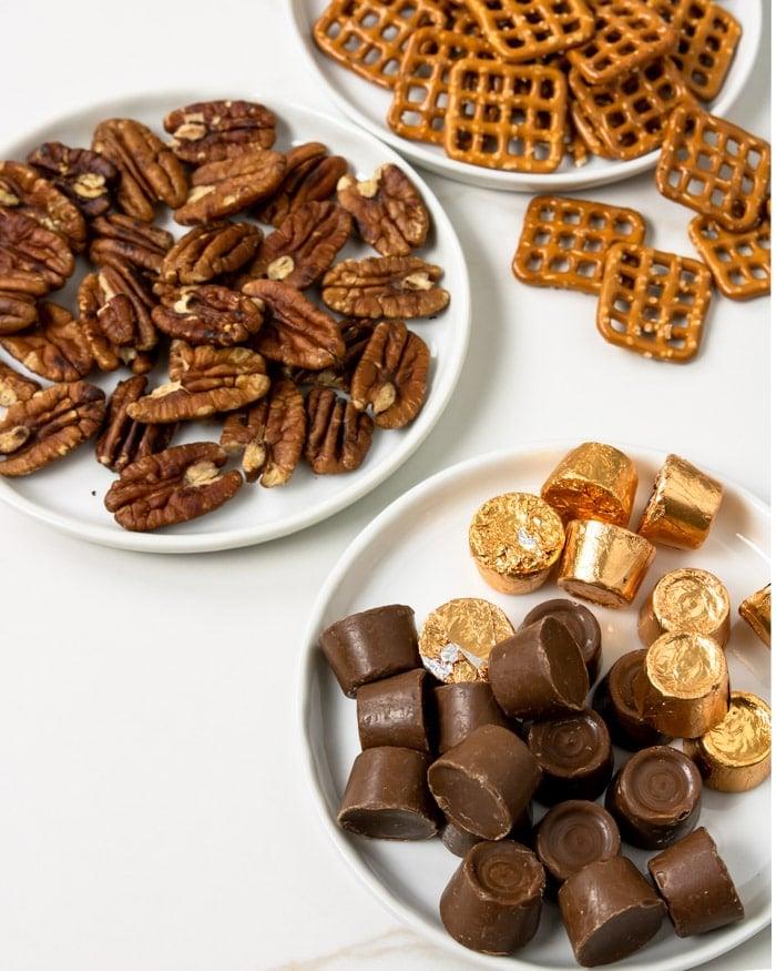 Rolo Pretzel Turtle ingredients on white plates: Rolo candy, pecans, pretzels
