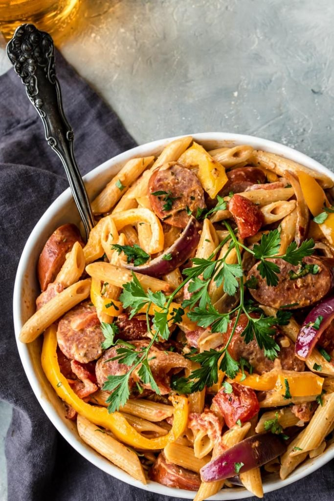 cajun pasta with peppers and sausage topped with parsley
