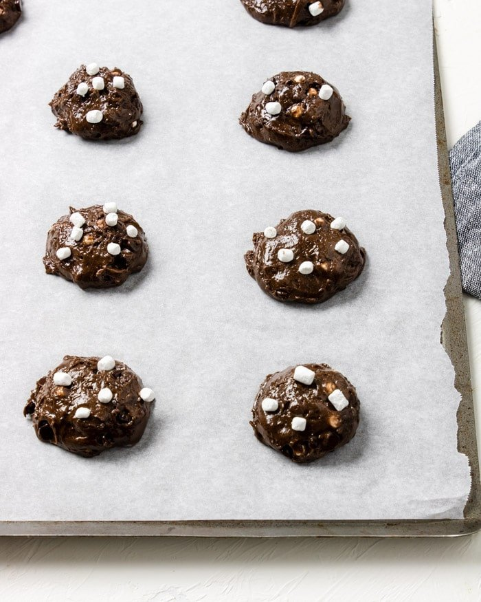 raw cookie dough balls on parchment lined cookie sheet with marshmallow bits placed on top of cookies
