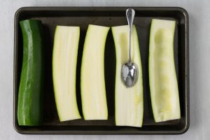 step by step how to make a zucchini boat by scooping out the center