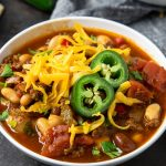 a bowl of chili topped with cheese and jalapenos