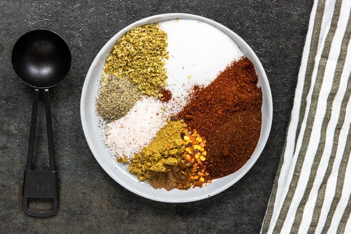 a plate of herbs and spices for chili