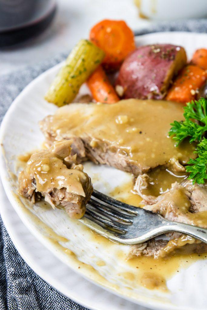 Tender Instant Pot Pork Roast on a fork with gravy