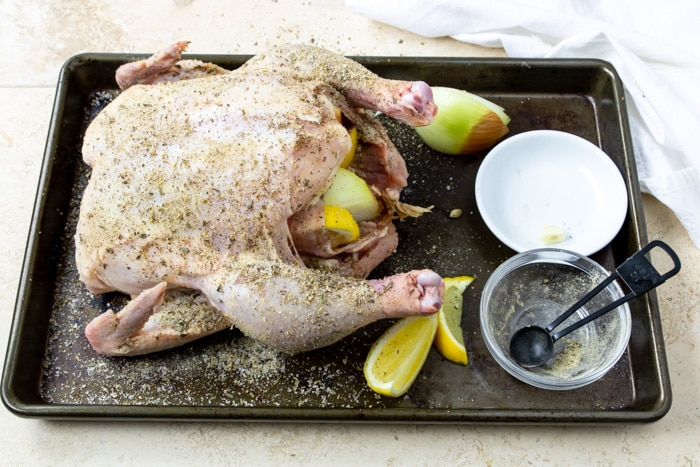 chicken seasoned with salt and herbs, stuffed with lemons and onions