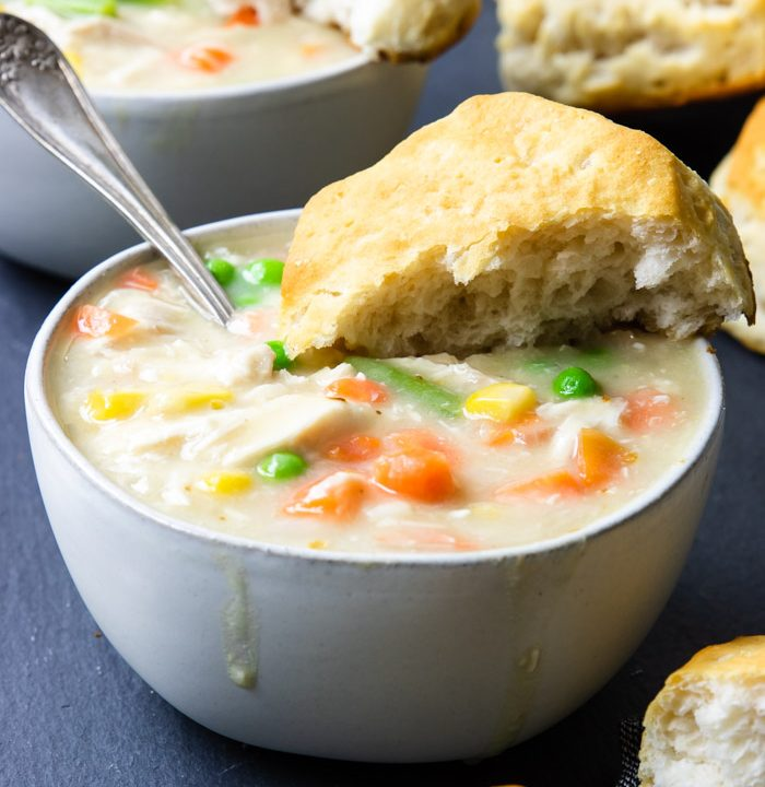 Chicken and biscuits in a white bowl with biscuits in the background