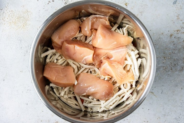 Step 4: Lay the quartered chicken breasts on top of the noodles