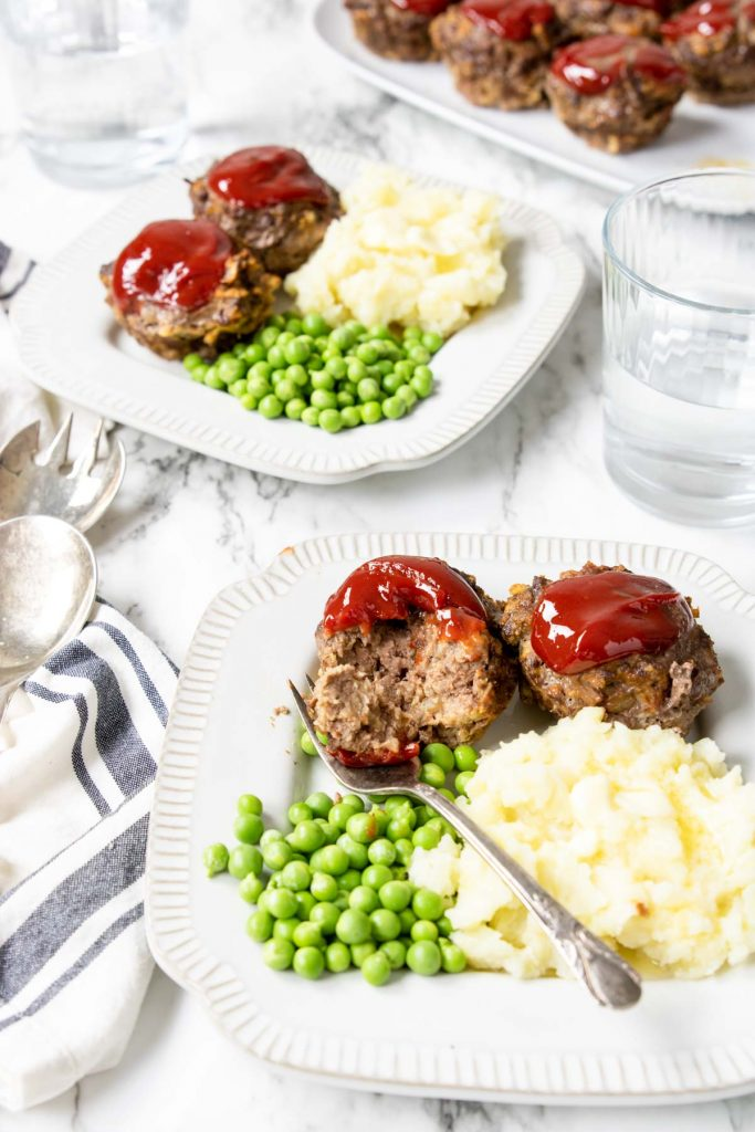 a table with two plates full of meatloaf muffins, peas and mashed potatoes