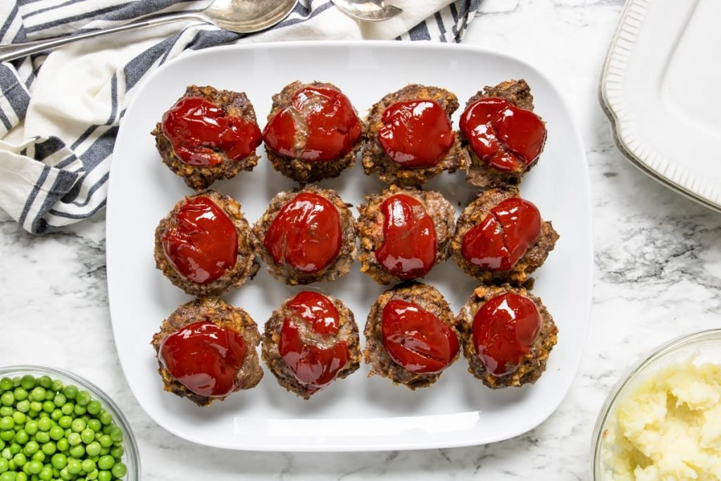 12 meatloaf muffins plated on a white plate surrounded by a bowl of peas and a bowl of mashed potatoes