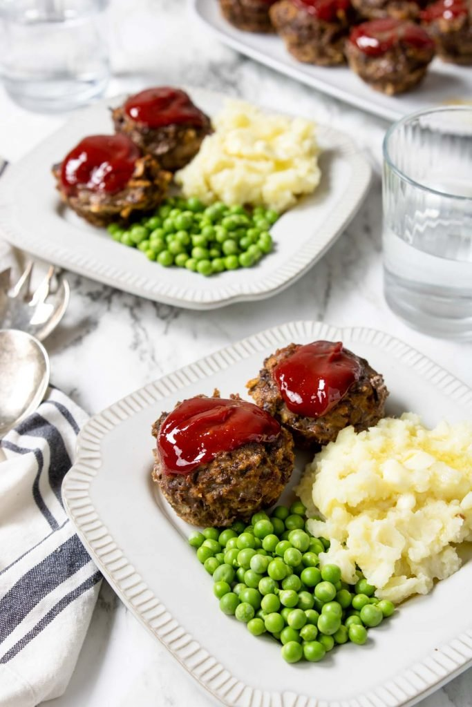 Two plates with meatloaf muffin cups, peas and mashed potatoes