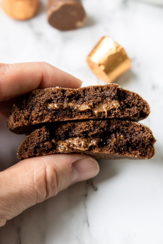 Chocolate Rolo Cookie cut in half showing the chocolate caramel center